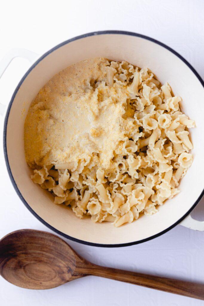 corn pasta sauce being stirred into pasta